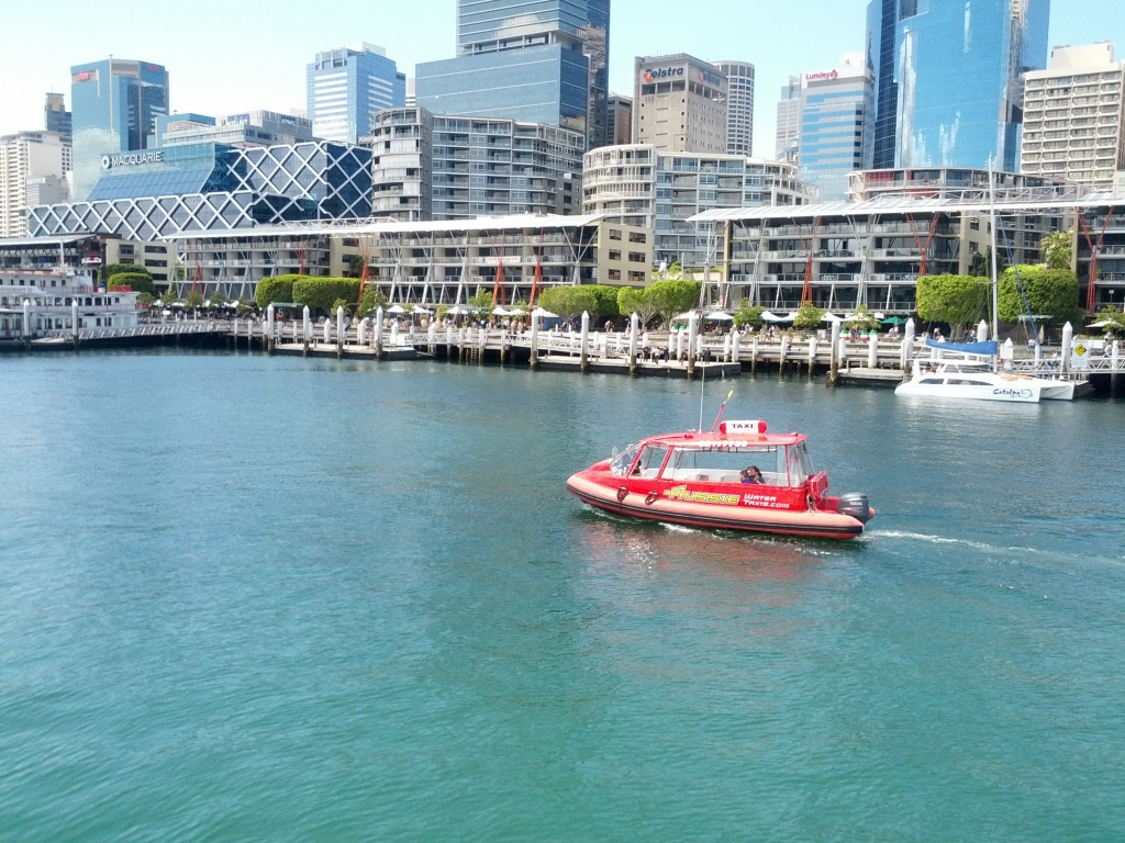 A water ferry cruises through Darling Harbour, near the maritime museum.